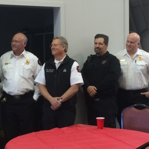 Fire Chief Mitch Flynn, Deputy Chief Mike Holzmueller, Battalion Chief Andrew Rossow, Battalion Chief Doug Fournier listen as a letter from Mayor Kassel is read